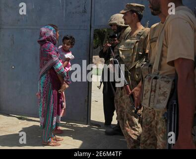 A woman carrying a girl walks past army soldiers who are standing guard at an entrance gate, after suicide bombers attacked a Christian neighbourhood in Khyber Agency near Peshawar, Pakistan, September 2, 2016. REUTERS/Fayaz Aziz Stock Photo