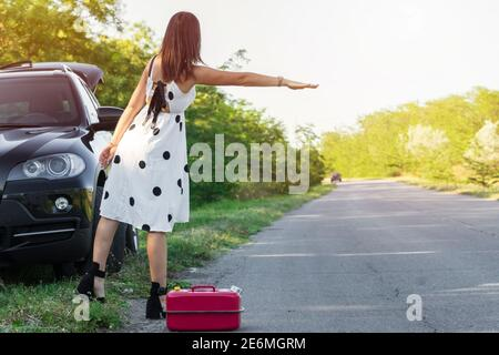 girl catches a car on the track. young woman near broken car on the road - Stock Photo