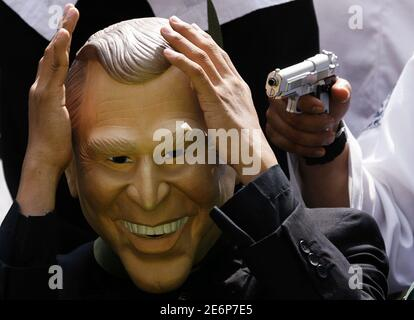 A toy gun is pointed at a protester wearing a mask of U.S. President George W. Bush during demonstration against Bush's planned visit, in Jakarta November 19, 2006. REUTERS/Beawiharta (INDONESIA) - Stock Photo
