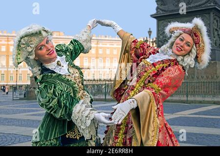 Two Russian women in 18th century period dresses posing for tourists by the Hermitage Winter Palace on Palace Square in the city St Petersburg, Russia - Stock Photo
