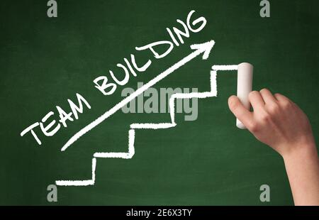 Hand drawing TEAM BUILDING inscription with white chalk on blackboard, business concept