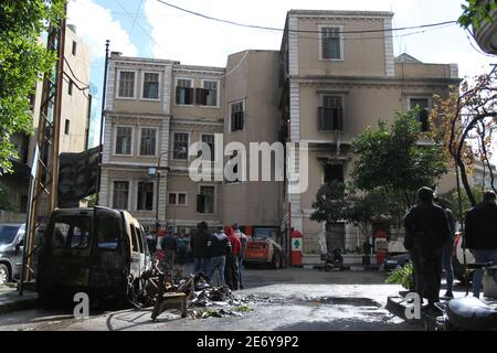 Tripoli, Lebanon. 29th Jan, 2021. People gather at a building damaged by protesters in Tripoli, northern Lebanon, on Jan. 29, 2021. Lebanese top officials condemned on Friday violent protests that took place in Tripoli in the past four days which left hundreds of people injured while killing one young man, the National News Agency reported. Credit: Khaled/Xinhua/Alamy Live News - Stock Photo