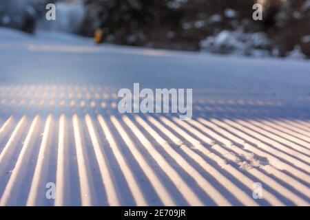 Close-up perspective of freshly groomed ski run slope in the forest, Bansko, Bulgaria