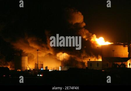 Albanian firefighters try to contain a fire at a fuel depot in the port city of Shengjin, some 70 km (44 miles) northwest of the capital Tirana, December 17, 2006. Firefighters worked all Sunday using retardant foam water and sand to prevent the fire from spreading to two bigger depots.   REUTERS/Arben Celi