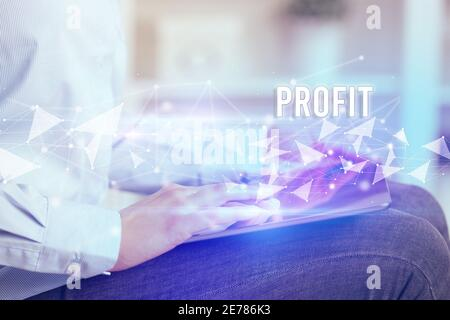 Close up hands using tablet with PROFIT inscription, modern business technology concept
