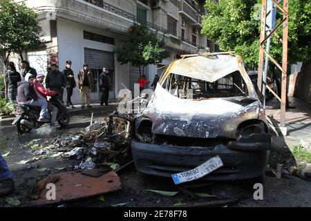 Beijing, Lebanon. 29th Jan, 2021. People look at a burnt vehicle in Tripoli, northern Lebanon, on Jan. 29, 2021. Lebanese top officials condemned on Friday violent protests that took place in Tripoli in the past four days which left hundreds of people injured while killing one young man, the National News Agency reported. Credit: Khaled/Xinhua/Alamy Live News - Stock Photo