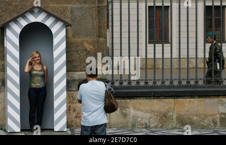 A tourist poses for a picture in an abandoned guarding post of the Prague Castle as a Czech Army soldier passes by, June 4, 2007, before the whole area was cleared from tourists due to security reasons. U.S. President George W. Bush arrives to the Czech Republic for two-day working visit.    REUTERS/Petr Josek (CZECH REPUBLIC)