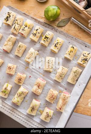 Metallic tray with four rows of raw sausage rolls on it over a white baking paper. A grated lime is next to the tray on a wooden table.