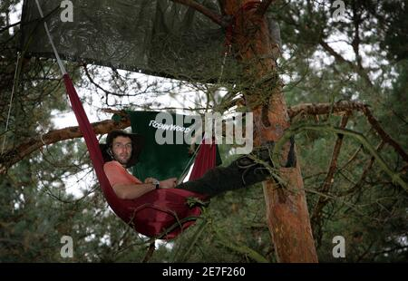 An activist from Robin Wood, an environmental organisation, sits in a tree in a sealed-off forested area called 'Bannwald' before the start of construction works on a new runway near Frankfurt's Rhine-Main airport September 11, 2005. Police expect protesters and environmental activists as construction for the controversial new runway will start next week. REUTERS/Kai Pfaffenbach  KP//CCK - Stock Photo