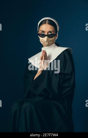 Medieval young woman as a nun in vintage clothing and golden face mask praying on dark blue background. Concept of comparison of eras, fashion, ad, healthcare. Royal person protected from covid. - Stock Photo