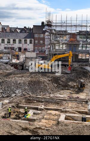 Demolition site (rubble, machinery, excavator demolishing, digger, building shell, archaeologists working in trench) - Hudson House, York, England UK.