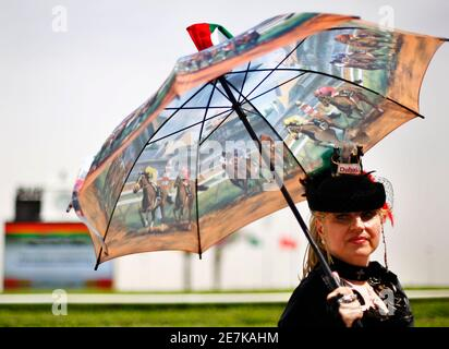 Katharina Dietrich of Germany poses with her umbrella along the race track ahead of the Dubai World Cup March 28, 2009. The Dubai World Cup, with a cash prize of $6 million, is horse racing's richest prize. REUTERS/Steve Crisp (UNITED ARAB EMIRATES SPORT HORSE RACING) - Stock Photo