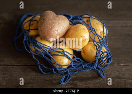 Heart-shaped red potatoes with white potatoes in a blue eco-grid on a wooden background close-up.