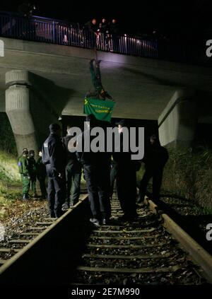 German police officers remove an anti-nuclear activist from the German environmental organisation Robin Wood hanging from a rope over a railway track in Oldendorf, between Lueneburg and Dannenberg November 10, 2008. The controversial shipment of eleven Castor containers with spent German nuclear fuel arrived in Dannenberg on Monday and will be loaded onto trucks before transportation to the nearby Gorleben intermediate storage facility in northern Germany after it left the French reprocessing plant of La Hague on Friday. The banner reads 'Stop Castor'. REUTERS/Christian Charisius (GERMANY) - Stock Photo