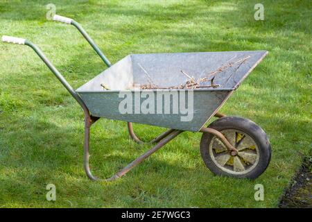 Wheelbarrow closeup on a lawn in garden in England, UK. Garden maintenance. - Stock Photo