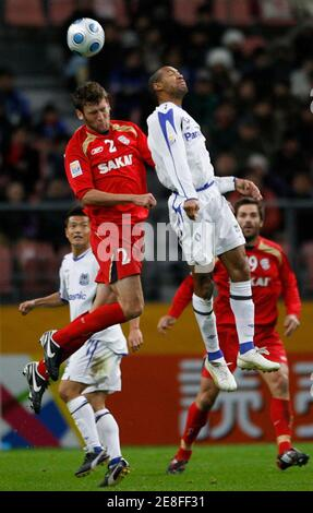 Robert Cornthwaite of Australia's Adelaide United battles for the ball with Lucas of Japan's Gamba Osaka during their FIFA Club World Cup soccer match in Toyota, central Japan December 14, 2008.  REUTERS/Yuriko Nakao (JAPAN)