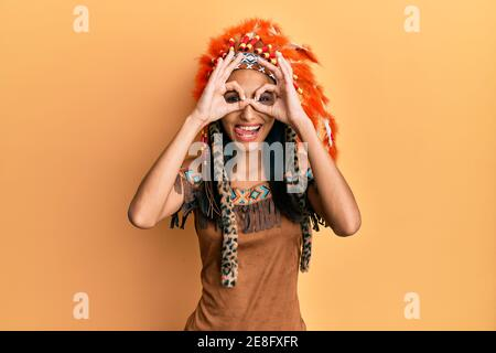 Young brunette woman wearing indian costume doing ok gesture like binoculars sticking tongue out, eyes looking through fingers. crazy expression. - Stock Photo