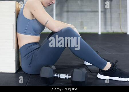 Side view of crop unrecognizable exhausted female athlete sitting on floor near dumbbells and resting after intense functional workout in sports cente