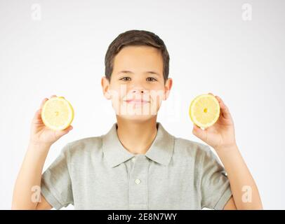 Portrait of lovely caucasian young boy shows two lemon slices.Boy look to a camera.