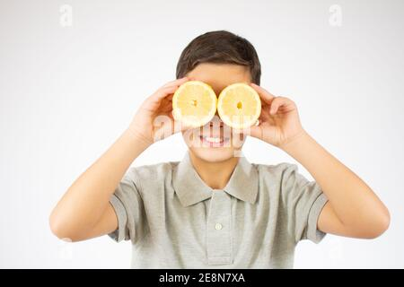 Happy ginger boy covering his eyes with lemons and smile on a white studio wall