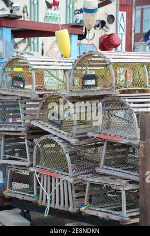 stacks of wooden lobster traps and buoys in nautical setting