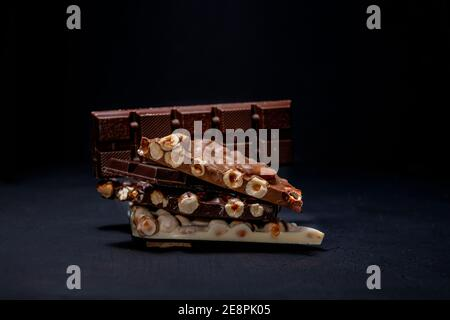 Dark and white chocolate with hazelnuts on a black background