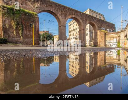 Frequent rain showers create pools in which the wonderful Old Town of Rome reflect like in a mirror. Here in particular Piazza di Porta Maggiore