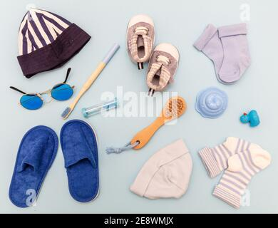 Baby boy accesories, baby shower flat lay. Blue color clothes and supplies for newborn child on pastel blue background, top view - Stock Photo