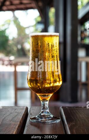 A glass of cold beer amber color with condensation on a wooden table in a pub, bar. Alcohol drink. Summer leisure concept