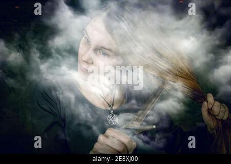 portrait of young long haired woman wearing a medieval costume. standing pose with a sword at her hair at dark studio background Stock Photo