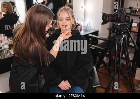 Woman make makeup for attractive blond hair woman in studio. Video of makeup artist applying cosmetics for beautiful model
