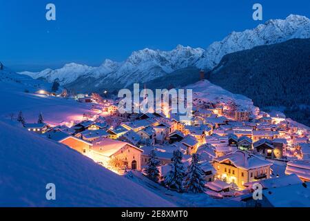 Traditional alpine village of Ardez covered with snow at dusk, canton of Graubunden, Engadine, Switzerland