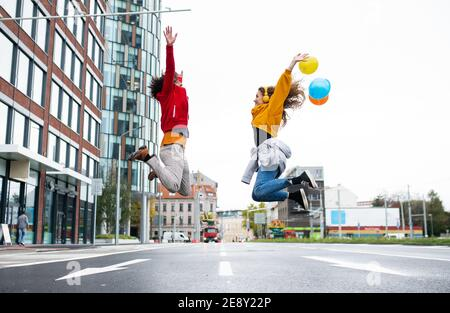 Young couple with balloons jumping outdoors on street, video for social media concept. Stock Photo