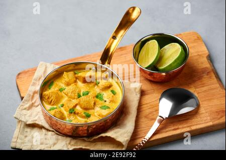 Chicken Korma in copper pan on gray concrete table top. Indian cuisine meat curry dish with coconut milk masala. Asian food Stock Photo