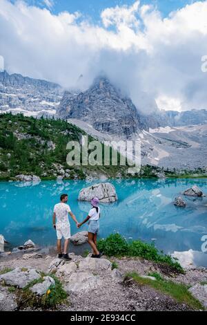 Beautiful Lake Sorapis Lago di Sorapis in Dolomites, popular travel destination in Italy. Blue green lake in Italian Dolomites. Couple hiking in the Dolomites Italy