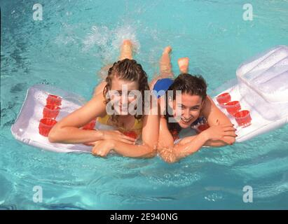 Sunny hot day for two model released teenage girls in swim suits playing on inflatable plastic Lilo in a rented Spanish holiday villa chlorinated swimming pool during a family summer holiday in Menorca Balearic Islands Spain in the 1980s archive historical image - Stock Photo