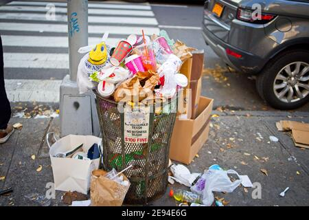 New York, NY, USA - Feb 1, 2021: Trash can overflowing with trash on a Manhattan sidewalk - Stock Photo