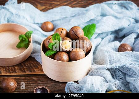Macadamia nuts in shell with mint leaves and honey on wooden background
