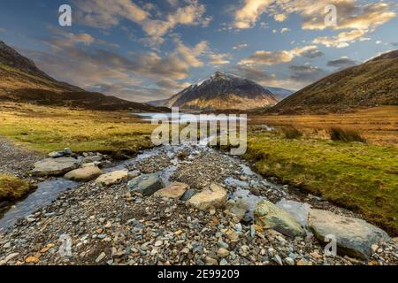 Stepping stones across the stream leading to Lake Idwal in Cwm Idwal Nature Reserve with Pen yr Ole Wen mountain in the background, Snowdonia, Wales