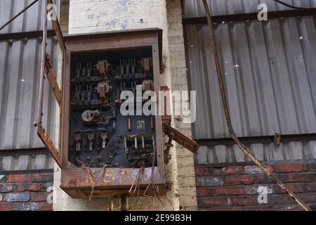 an old electrical consumer box in an abandoned factory - Stock Photo