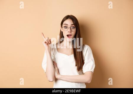 Creative young woman in glasses pitching idea, raising finger in eureka sign and gasping, have a plan, standing on beige background