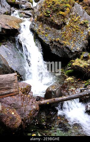 A small stream, cascading down from the mountains, breaking against the stones. Boki river, Altai, Siberia, Russia.