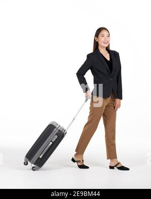Young asian women in black suit smiles as she walks dragging a black suitcase. Portrait on white background with studio light.