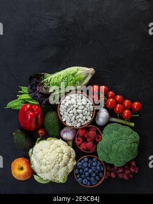 Healthy food background, trendy plant based diet products - fresh raw vegetables, berries, and beans.