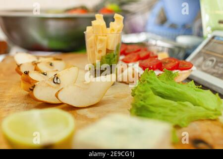 Cheese, fruit pear lemon salad on a wooden board. Bruschetta with tomatoes. - Stock Photo