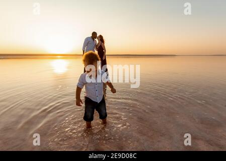 Portrait of little mixed race boy. Kissing parents on background. Happy multi ethnic family at the beach. Beautiful sunset