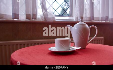 White china coffee pot and cup and saucer on red table below window