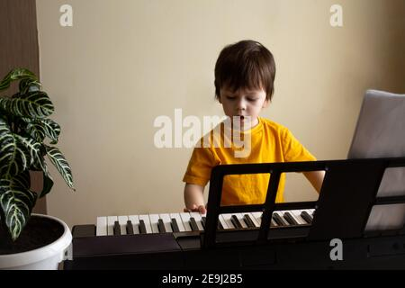 A boy playing the synthesizer. Toddler learning how to play piano. Child's hands on the keyboard. Early development and education concept