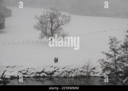People walking across a snow covered landscape with a tree in the background and a river in the foreground, photo taken from a slow moving train - Stock Photo