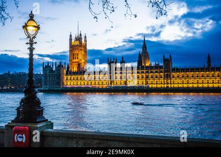 The Houses of Parliament along the river Thames in London at night.